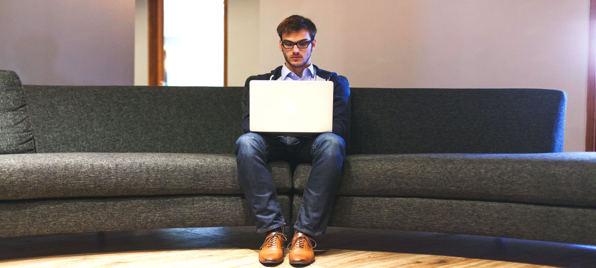 Student using computer sitting on couch