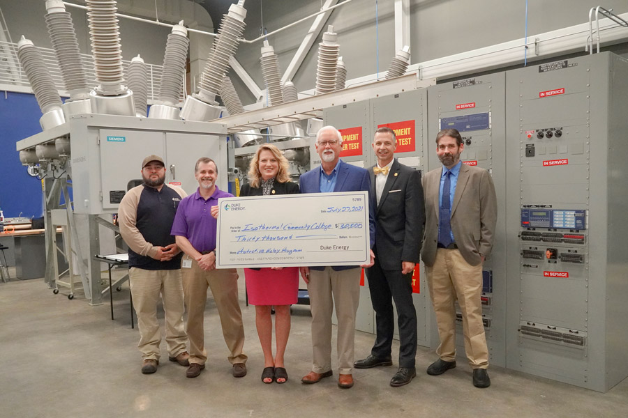 Representatives from Duke Energy Foundation and Isothermal holding oversized check in front of large substation equipment.