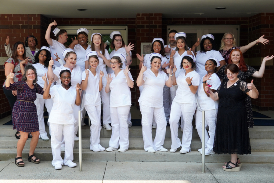 Nursing graduates with instructors in group.