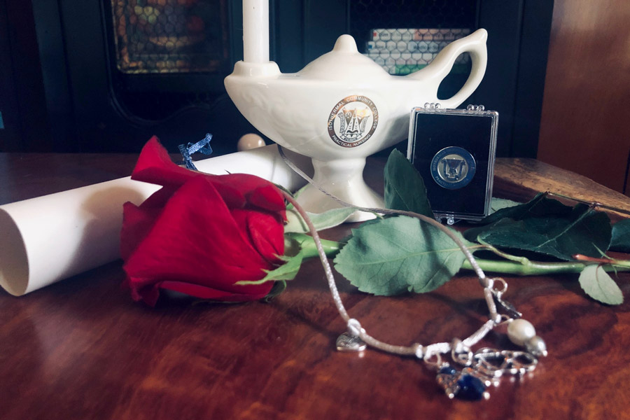 Practical Nursing Lamp and Pin on table with flowers, necklace, and rolled up diploma.